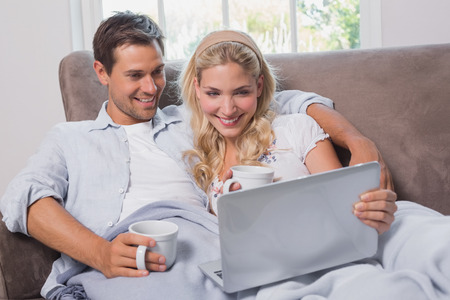 Relaxed loving young couple with coffee cups using laptop on sofa at home photo