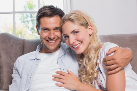 Portrait of a relaxed cheerful loving young couple sitting on sofa at home photo