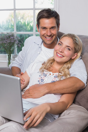 Portrait of a relaxed casual young couple using laptop in living room at home photo