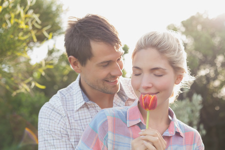 Close-up of a smiling young couple holding a flower in the\ park