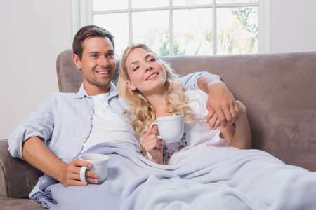 Relaxed loving young couple with coffee cups looking away in living room at home photo