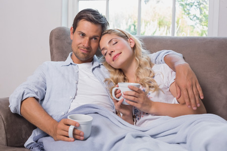 Relaxed loving young couple with coffee cups sitting on sofa at home photo
