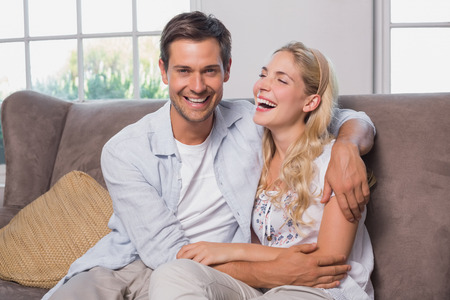 Relaxed cheerful loving young couple sitting on sofa at home photo