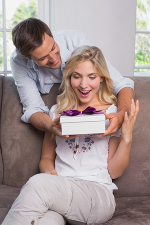 gifting: Smiling young man surprising cheerful woman with a gift box at home