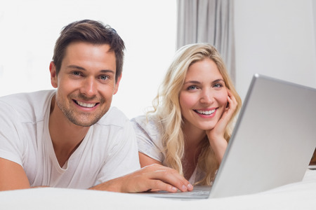Portrait of a relaxed casual young couple using laptop in bed at home photo
