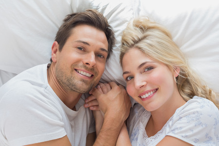 High angle portrait of a relaxed loving couple lying in bed at home photo