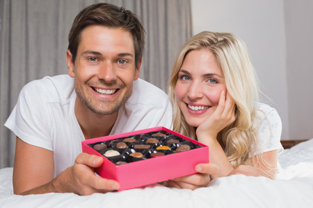 Portrait of a relaxed happy young couple with candies resting in bed at home photo