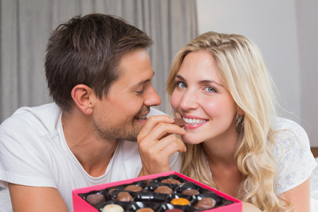 Relaxed happy young couple eating candies at home photo
