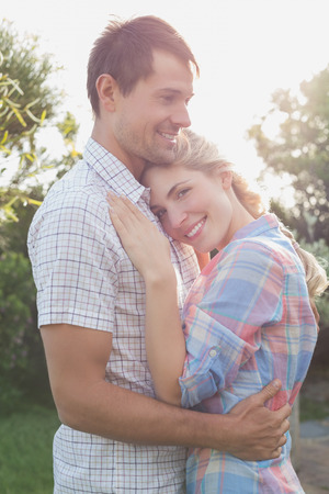 Side view of a smiling young couple embracing in the park photo