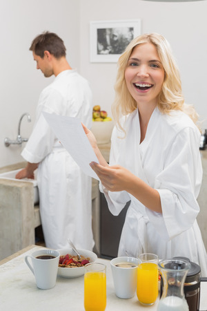 Smiling young woman holding document with man in background in the kitchen at home photo