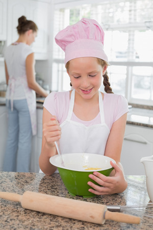 Young girl helping her mother prepare food in the kitchen at home photo