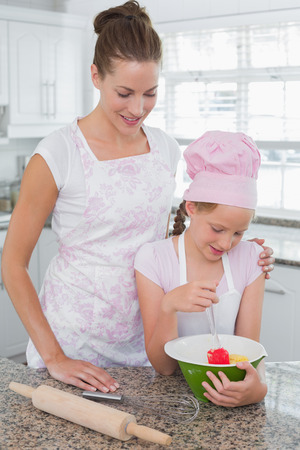 Portrait of a young girl helping mother prepare food in the kitchen at home photo