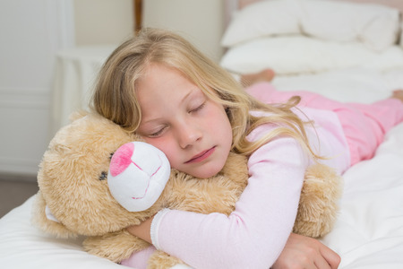 Close-up of a young girl sleeping with stuffed toy in bed at\ home