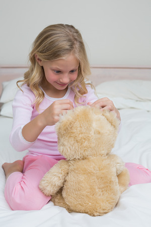 Relaxed young girl sitting with stuffed toy in bed at\ home