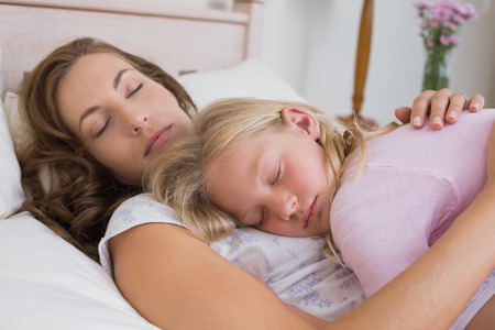 Side view of a young girl sleeping on mother in bed at home photo