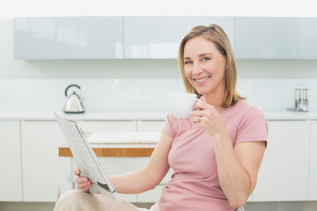 Portrait of a relaxed woman with newspaper having coffee in the kitchen at home photo