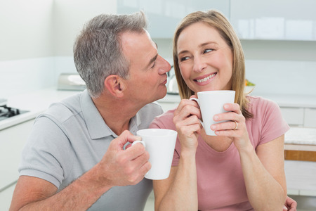 Close-up of a loving man kissing a happy woman with coffee cups in the kitchen at home photo