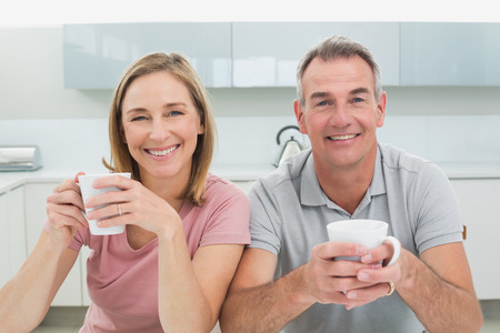 Portrait of a happy relaxed couple with coffee cups in the kitchen at home photo