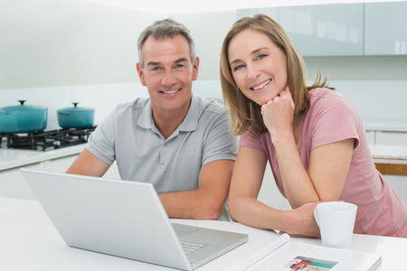 Portrait of a happy couple using laptop in the kitchen at home photo