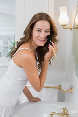 Portrait of a beautiful young woman applying make-up in the bathroom at home photo