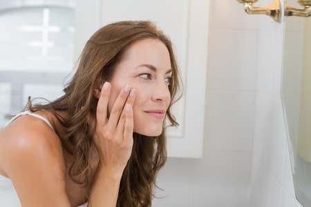 hand mirror: Side view of a beautiful young woman examining her face in the bathroom at home