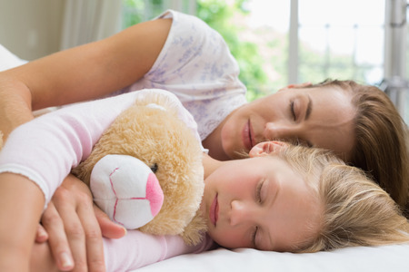 Young girl and mother sleeping peacefully with stuffed toy in bed at home photo