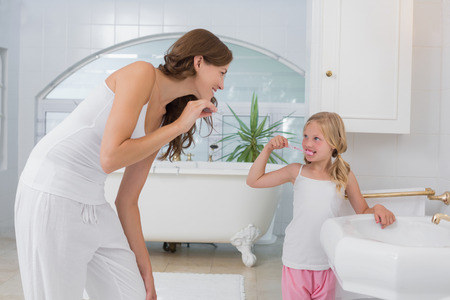 Little girl brushing teeth as she looks at her mother in the bathroom photo