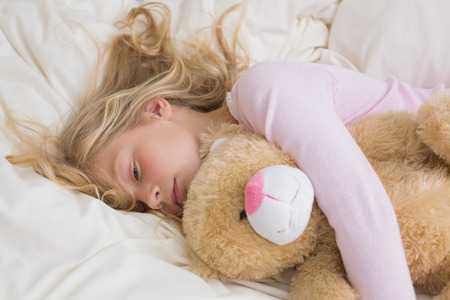 Young girl sleeping peacefully with stuffed toy in bed at home photo