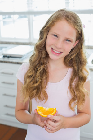 Portrait of a smiling young girl with a sweetlime slice standing in the kitchen at home Banco de Imagens