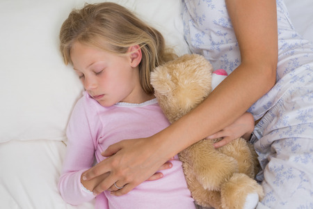 peacefully: Close-up of a young girl and mother sleeping peacefully with stuffed toy in bed at home