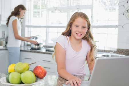 Portrait of a daughter using laptop with mother cooking food in background at the kitchen photo