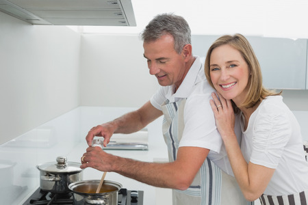 cook house: Side view of a happy couple preparing food in the kitchen at home Stock Photo