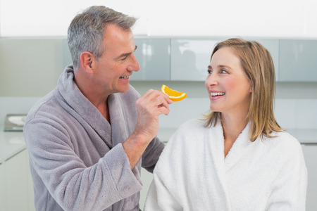 mature adult women: Happy man feeding woman orange slice in the kitchen at home Stock Photo