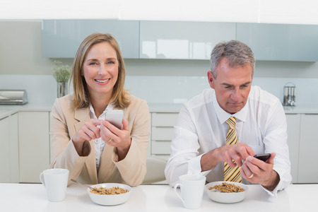 Business couple text messaging while having breakfast in the kitchen at home photo