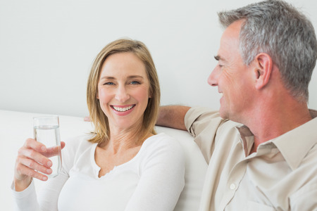 mature adult women: Relaxed couple with a glass of water in living room at home Stock Photo