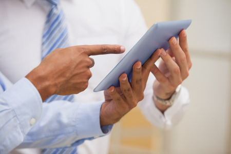 chinese businessman: Close-up mid section of two businessmen using digital tablet