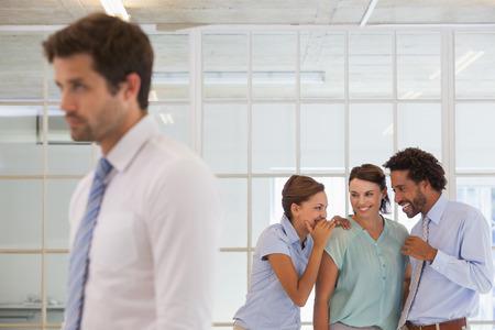 conflicto: Colegas que chismean con joven empresario triste en primer plano en una oficina brillante