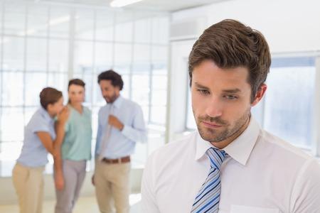 Collega's roddelen met droevige jonge zakenman op de voorgrond op een lichte kantoor