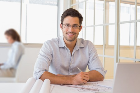 asian architect: Portrait of a smiling young businessman working on blueprints at the office
