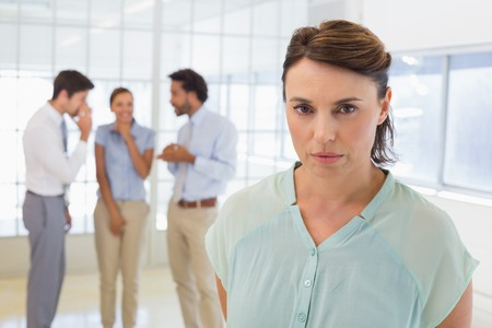 Colleagues gossiping with sad young businesswoman in foreground at a bright office Stock Photo
