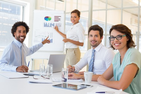 Portrait of a young businesswoman giving presentation to colleagues in a bright office