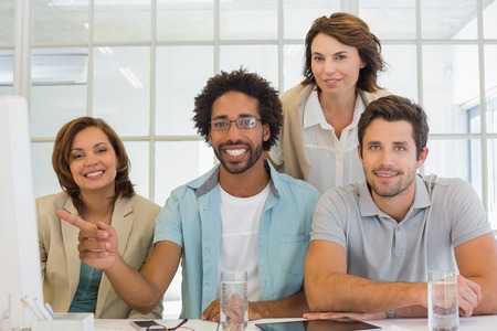 Group portrait of young business people with computer sitting at office desk photo