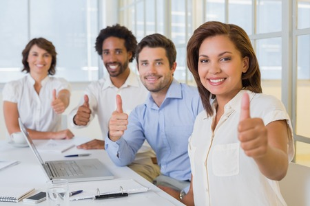 Portrait of happy business people gesturing thumbs up in meeting at the office photo