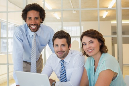 Portrait of three smiling young business people using laptop together at office desk photo