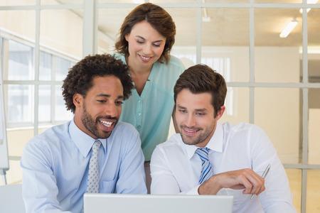 3 つのオフィスで一緒にノート パソコンを使用して若いビジネス人の笑顔