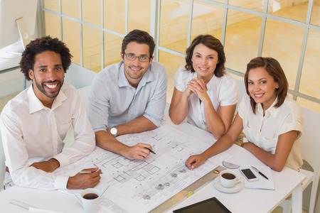 Portrait of smiling young colleagues working on blueprints in the office photo
