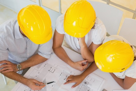 Top view of architects in yellow helmets working on blueprints at the office