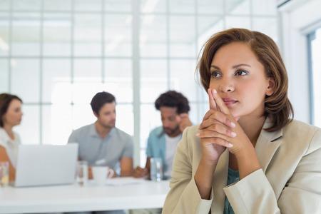Close-up van een ernstige zakenvrouw met collega's in ontmoetingen in de achtergrond op het kantoor