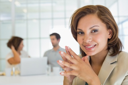 Close-up of a smiling businesswoman with colleagues in meeting in background at the office photo