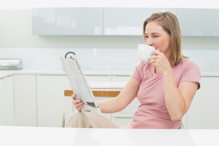 Relaxed woman reading newspaper while having coffee in the kitchen at home photo